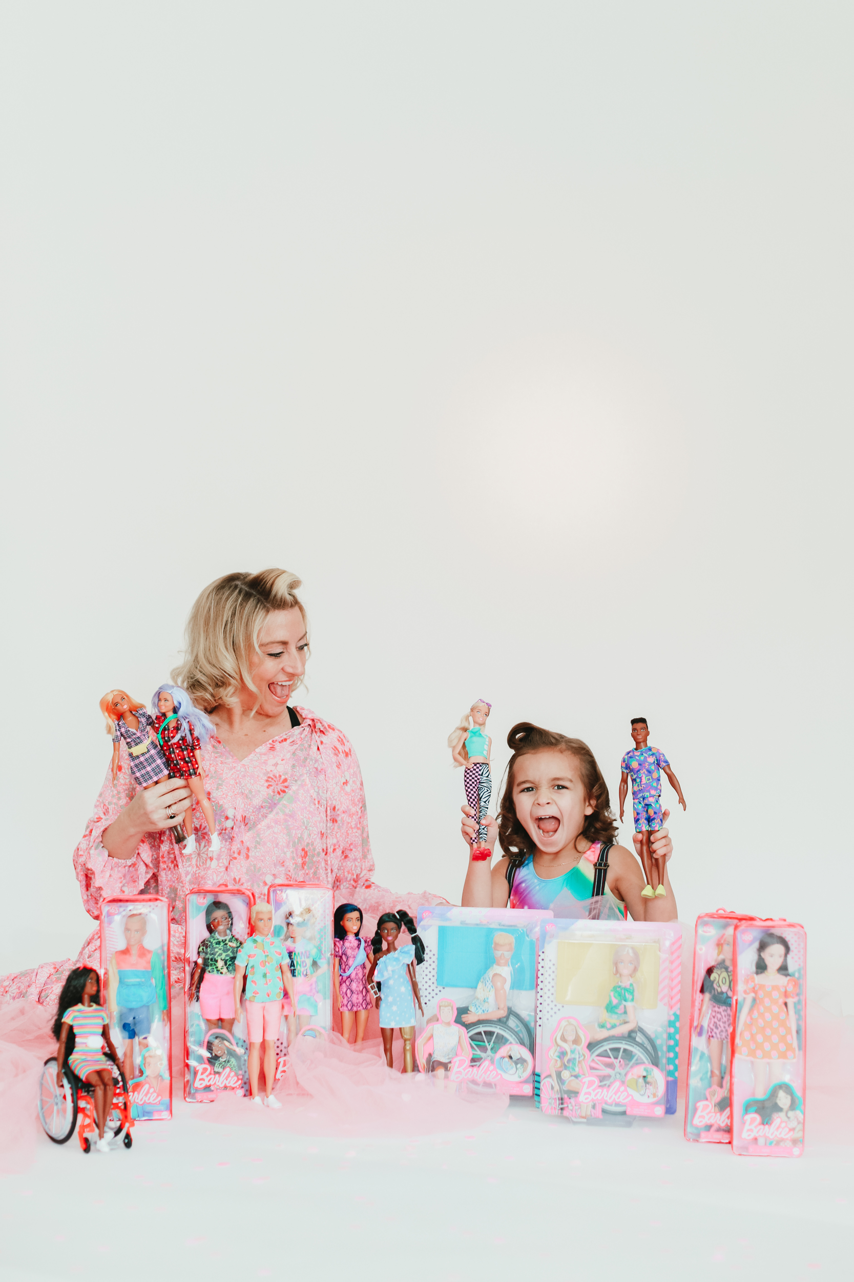 mom and kid playing with barbie dolls