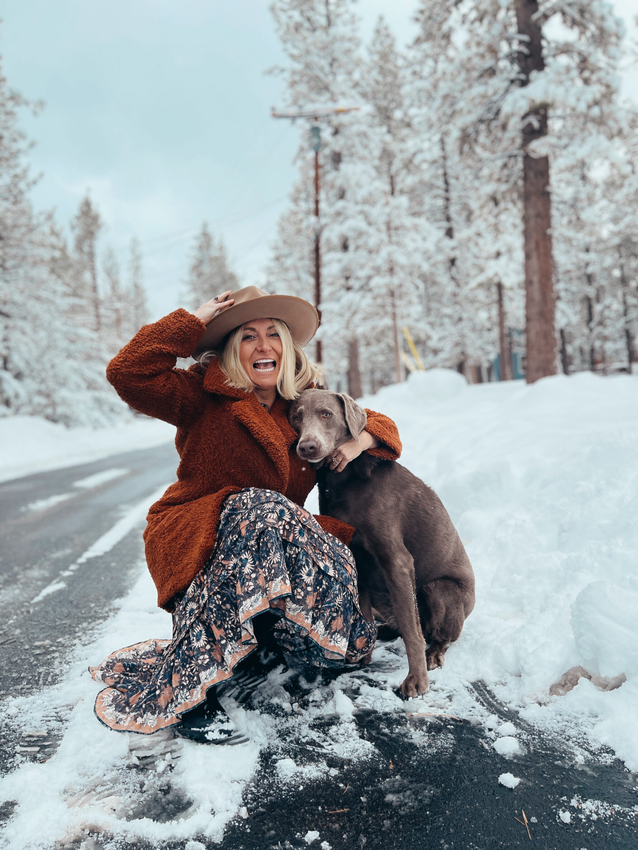 woman with her dog in the snow