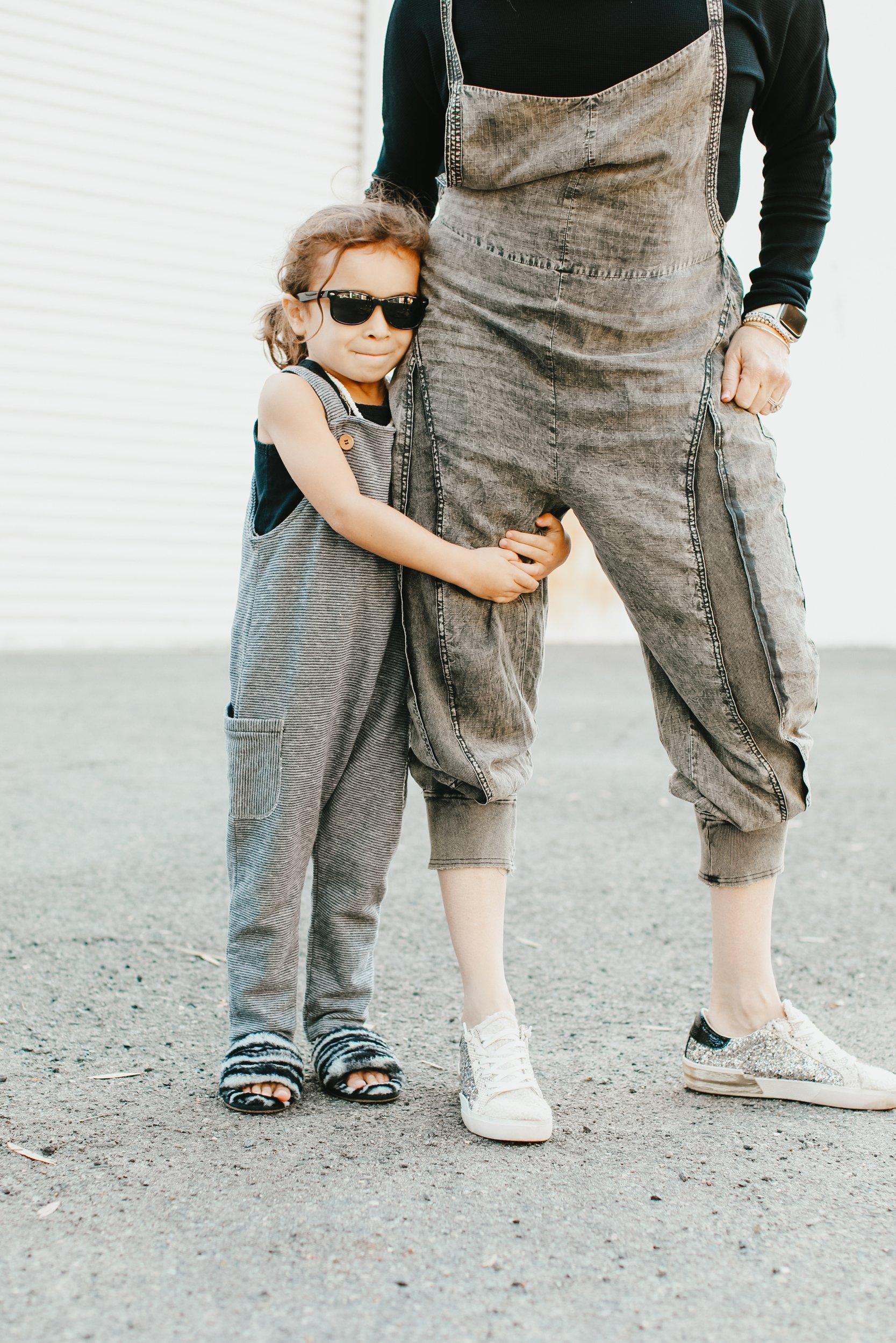 toddler holding onto mom's leg
