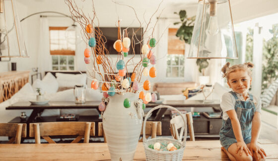 child on table with easter egg tree