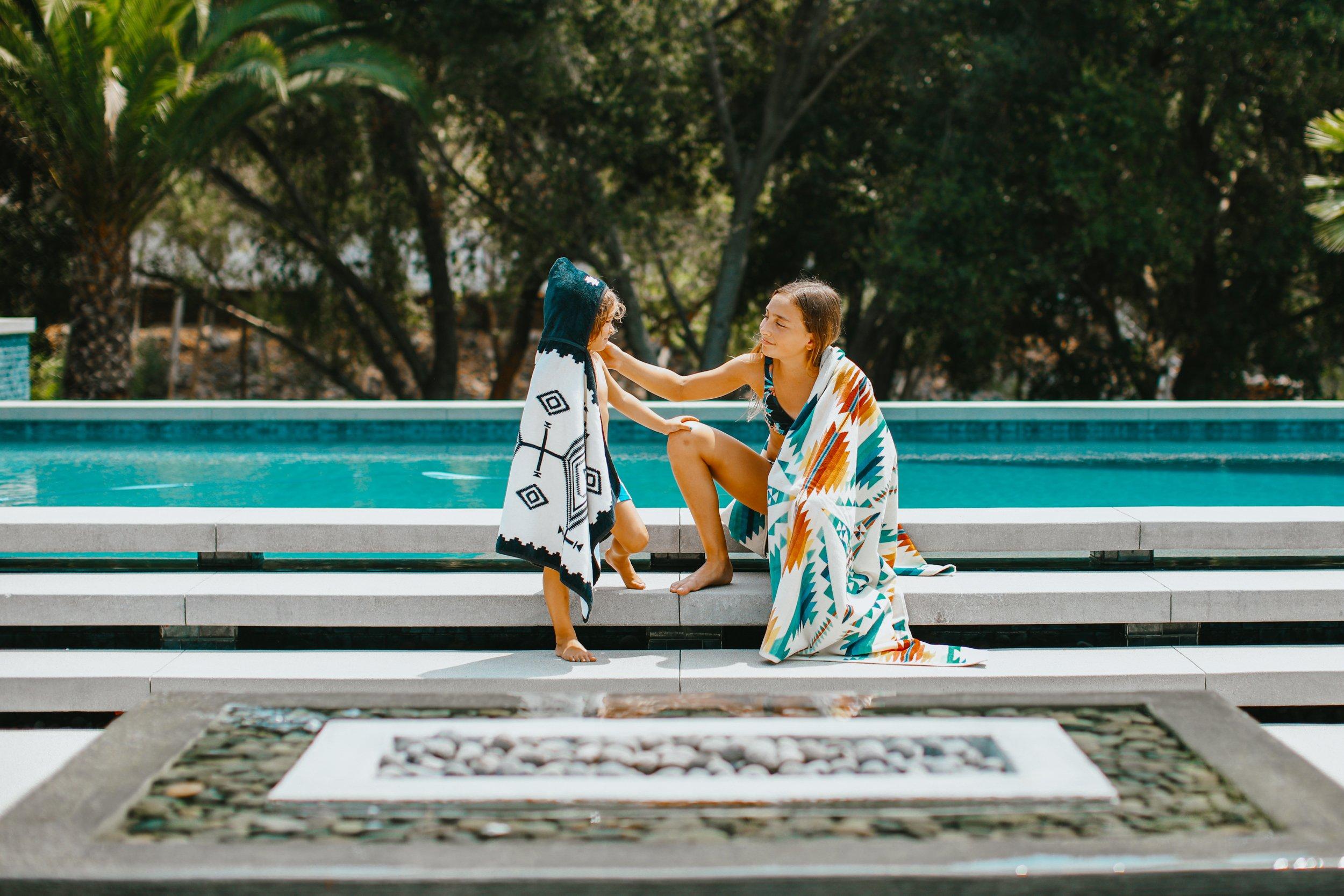 siblings sitting by pool