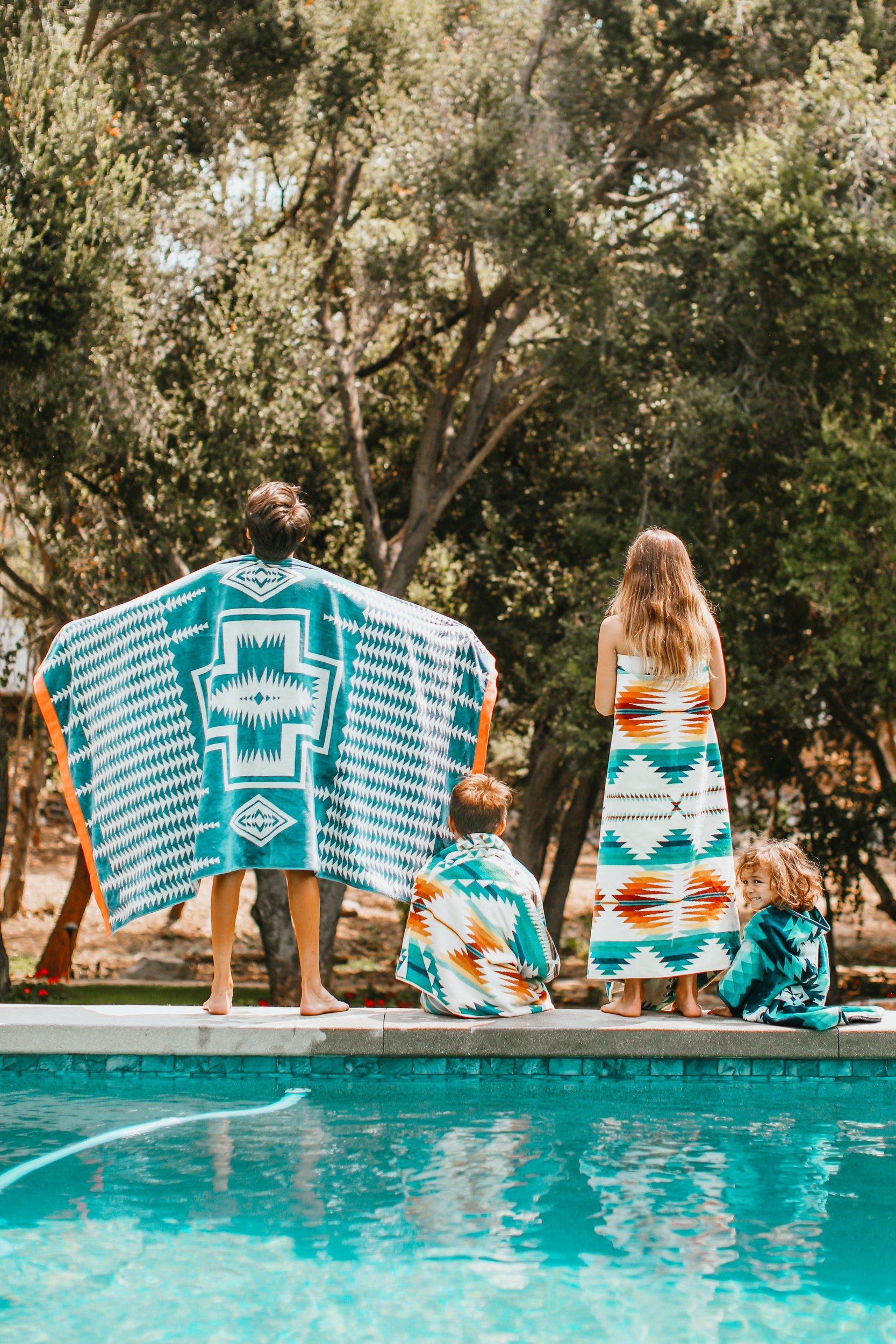 kids in towels by pool
