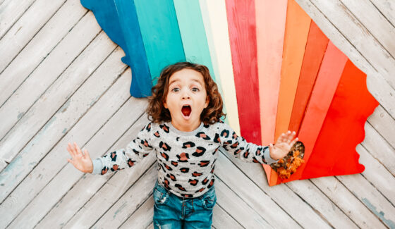 happy toddler by rainbow wall