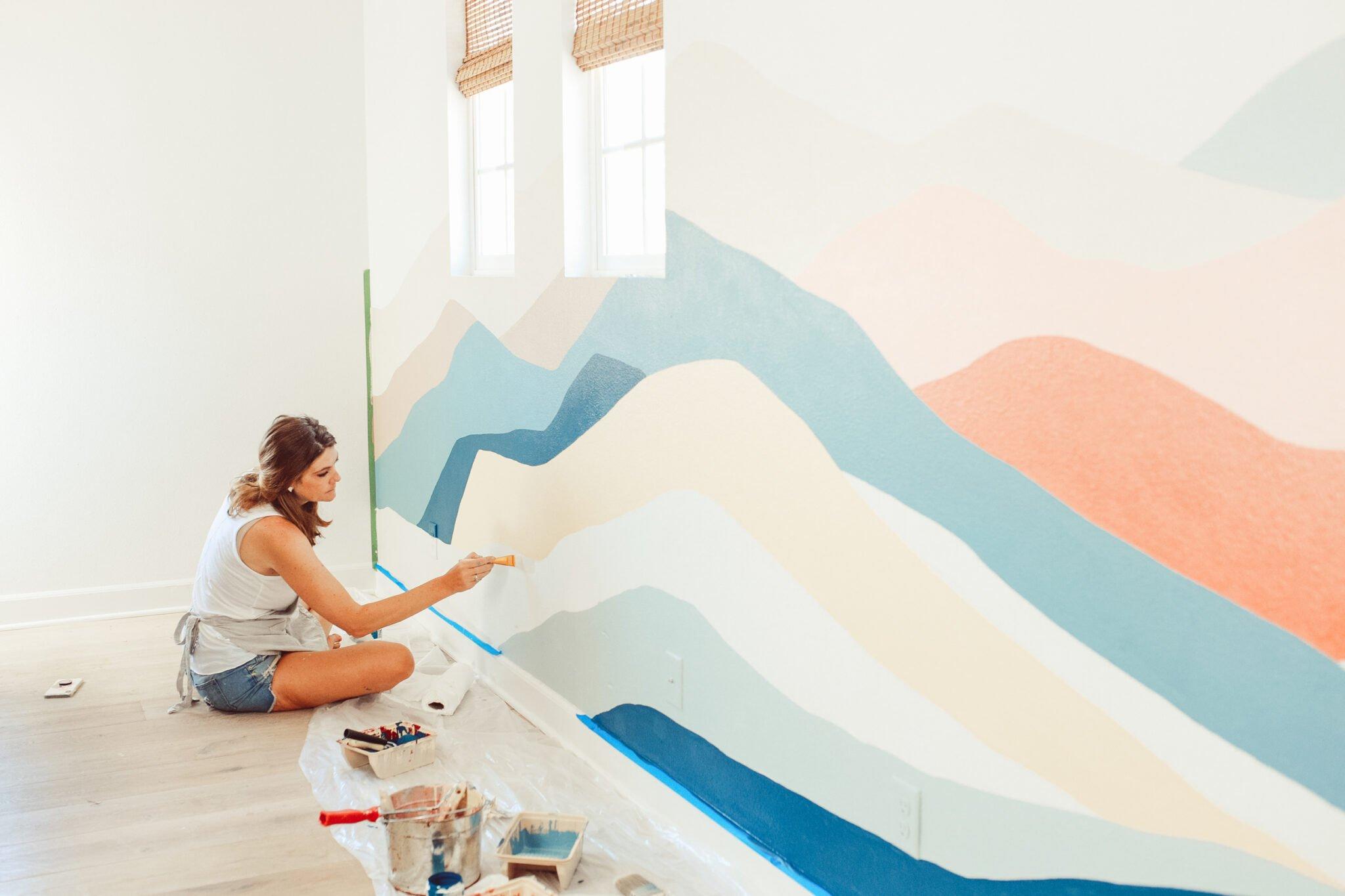 woman painting wall mural