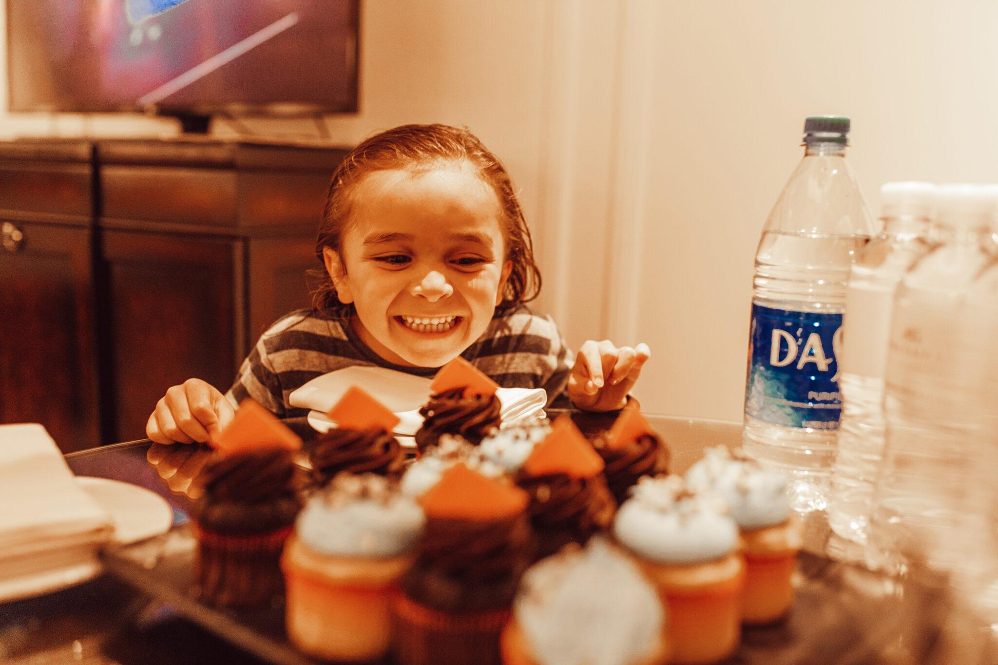 boy looking at cupcakes