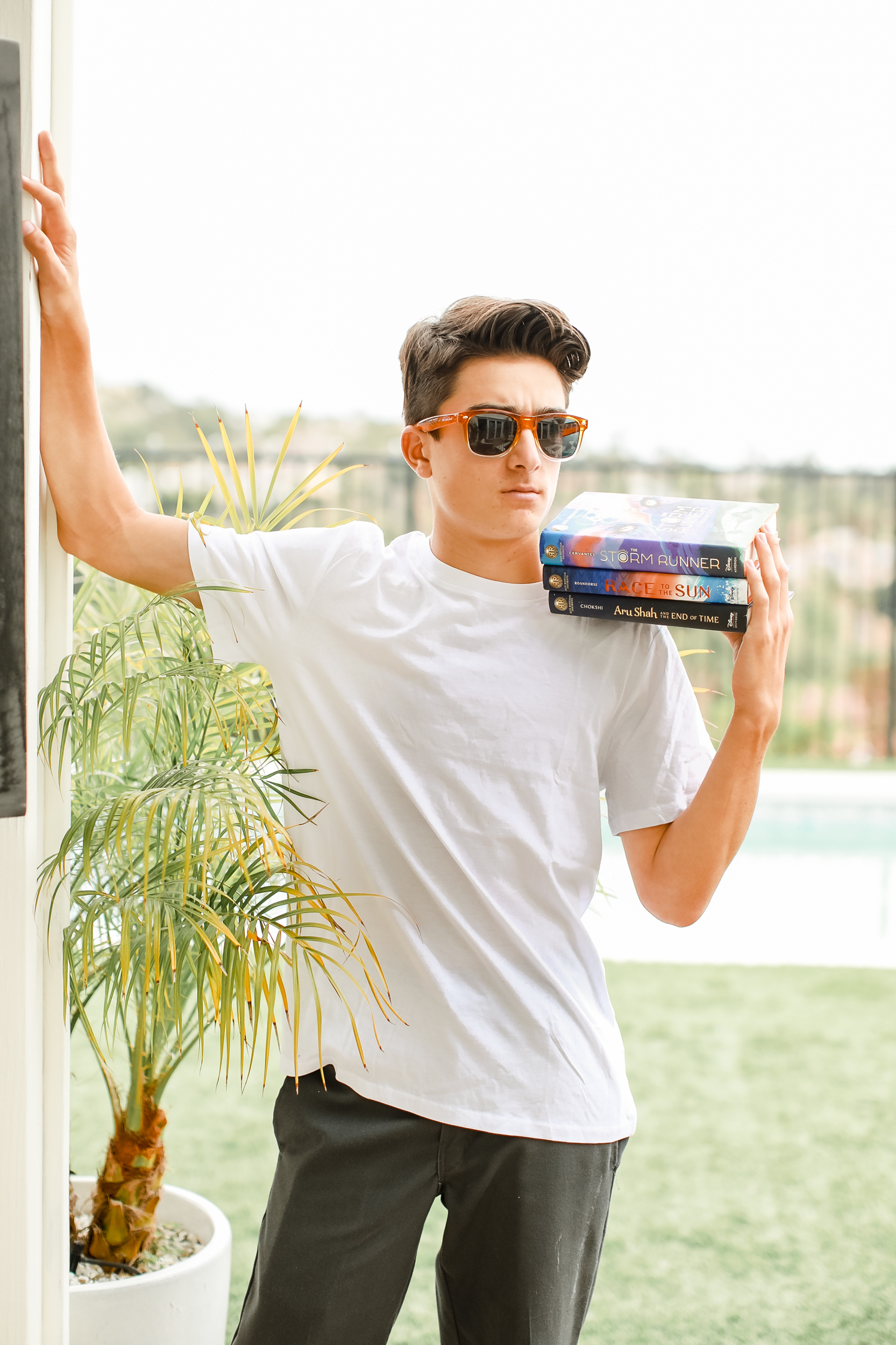 boy holding stack of books