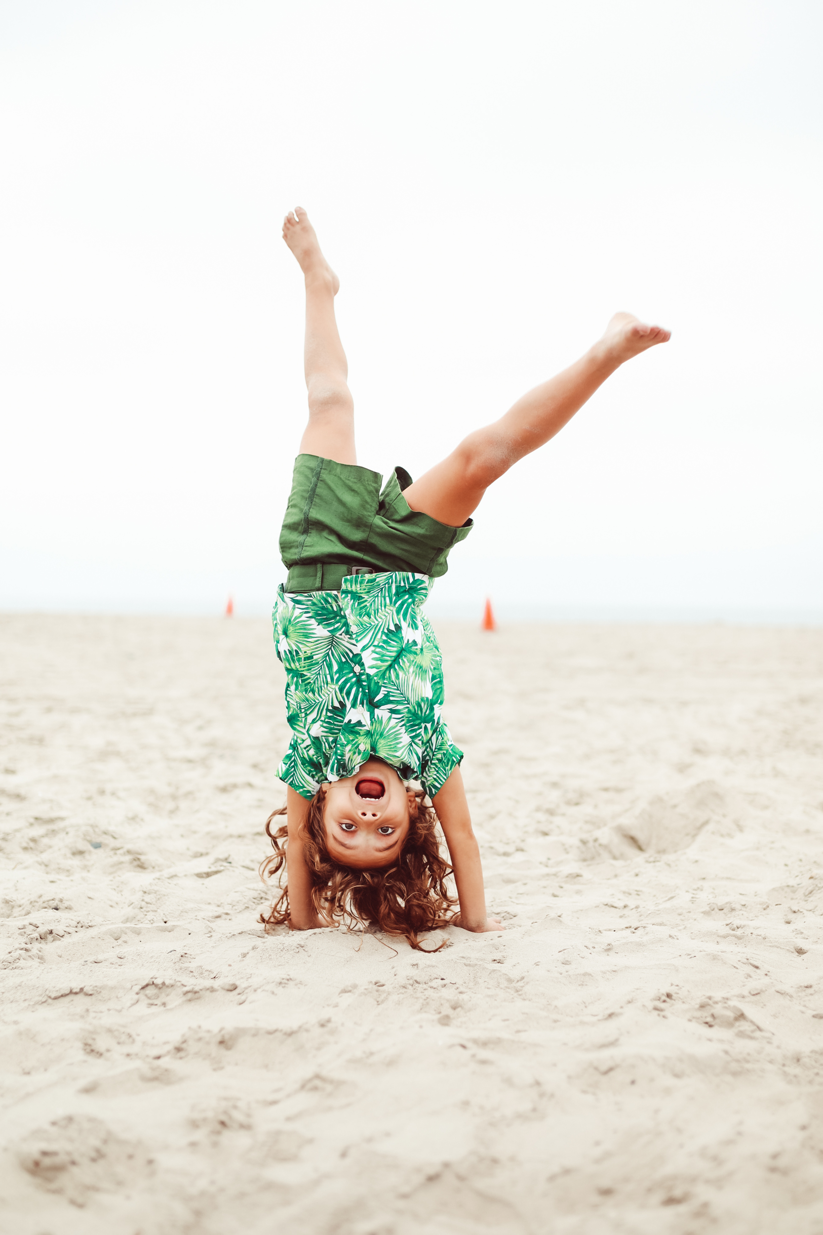 boy doing a cartwheel in the sand
