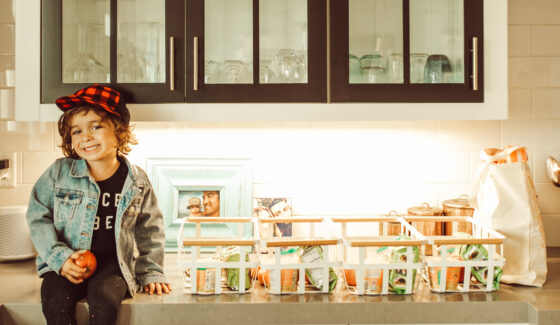 toddler sitting on kitchen counter with groceries